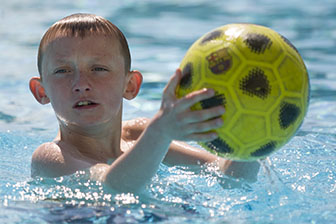 Closeup Portrait of a boy in the swimming pool with a football